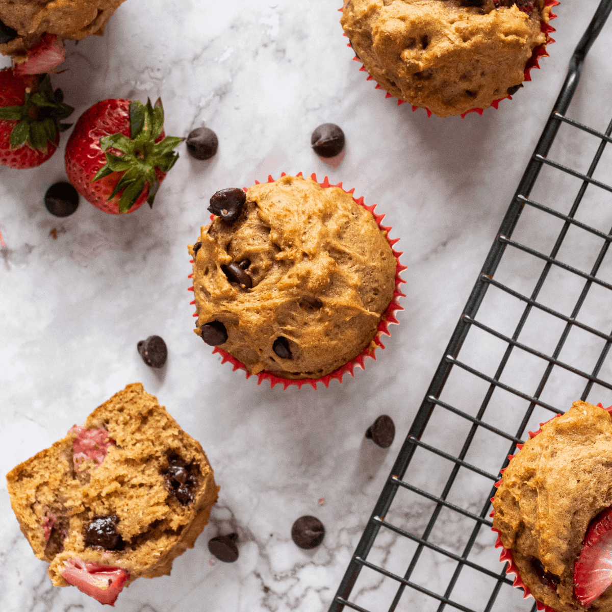 healthy Strawberry chocolate chip muffins next to strawberries.