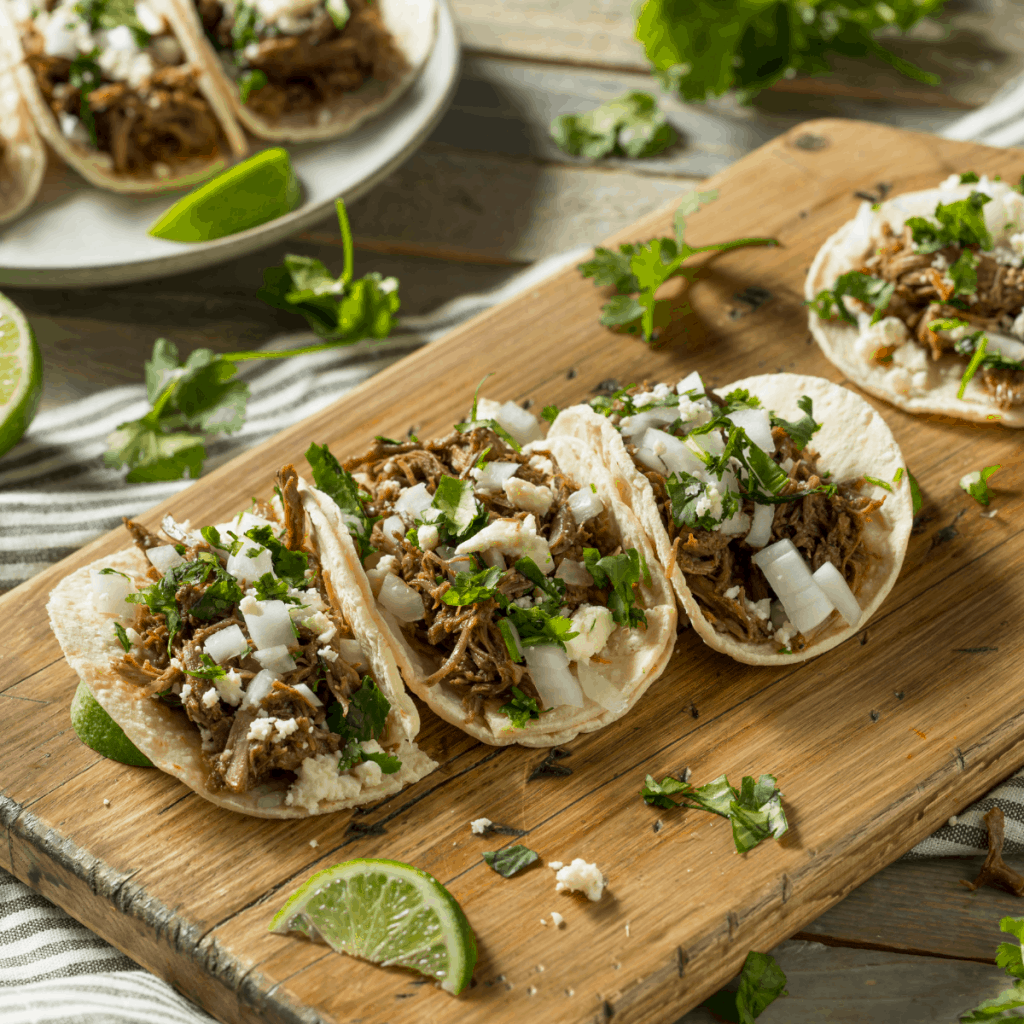 shredded pork tacos with onions and cilantro on top.