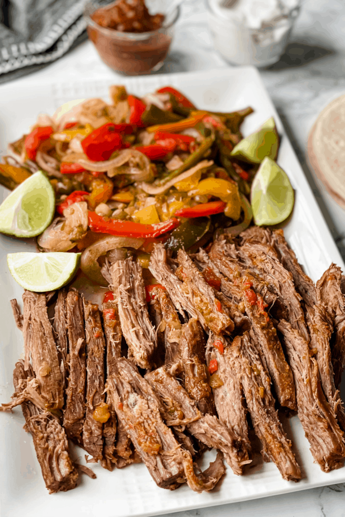 Sliced flank steak to use for fajitas on a white platter with onions and peppers.