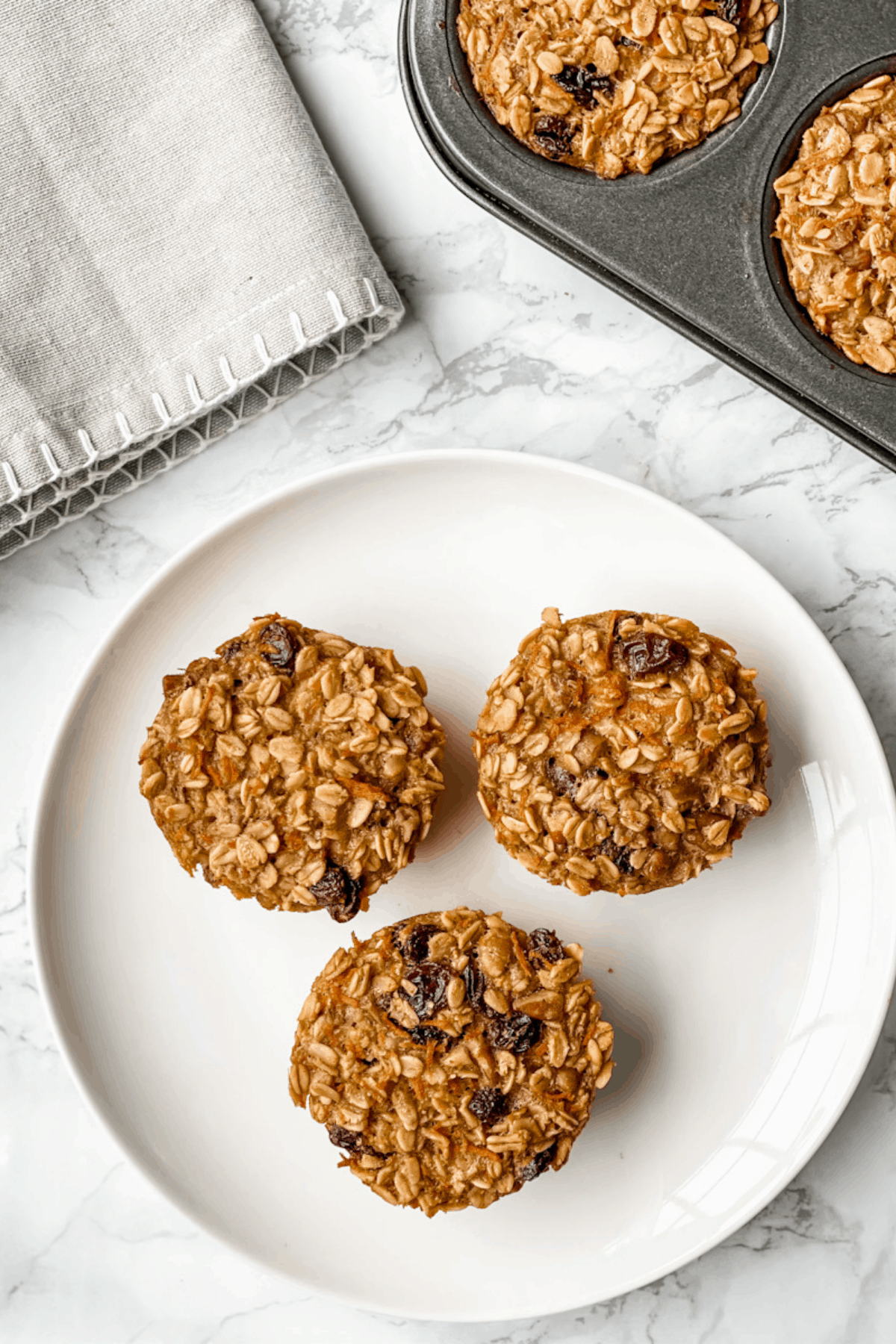 three baked carrot cake baked oatmeal cups on a plate.