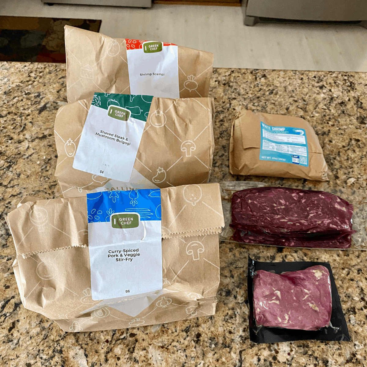 the green chef bags and proteins on the counter
