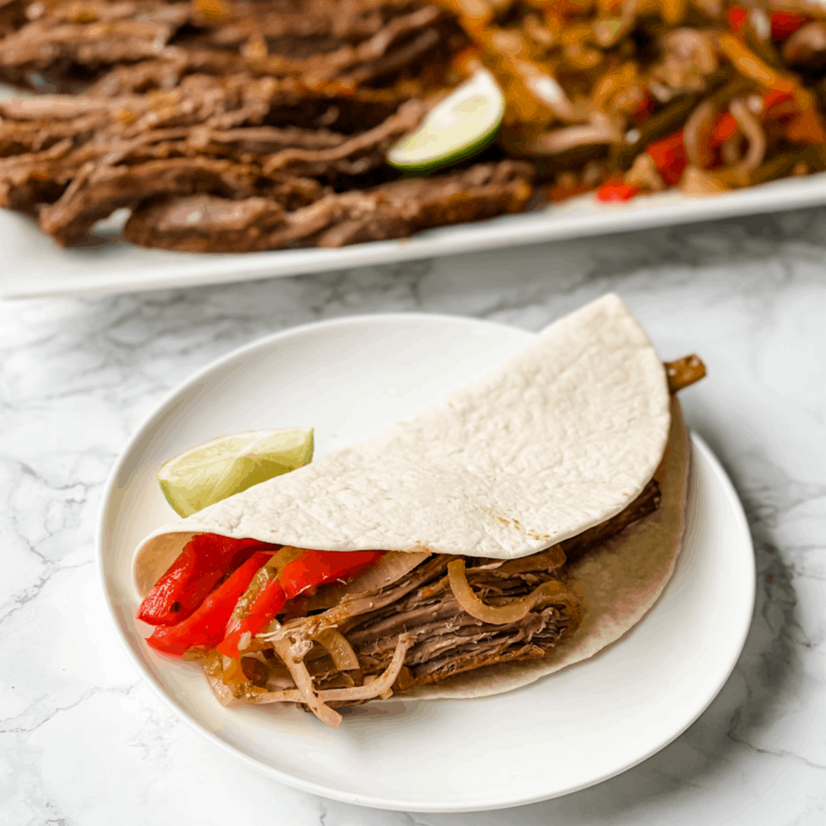 Steak fajita in a flour tortilla with a platter of sliced steak, onions, and peppers in the background.