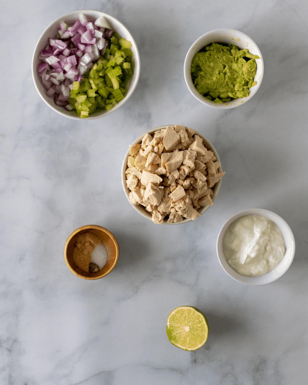 Ingredients for no mayo chicken salad. Chopped chicken, Greek yogurt, avocado, seasoning, and lime.