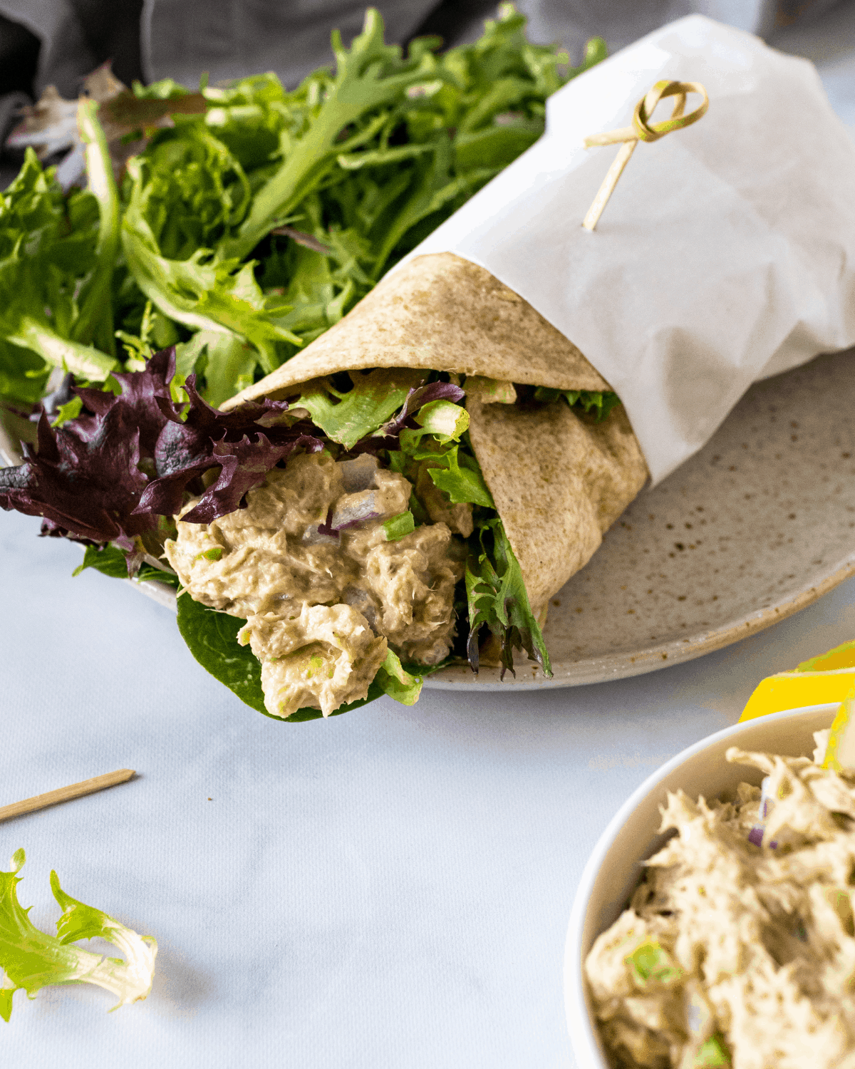no mayo tuna salad in a wheat wrap on a plate with greens.