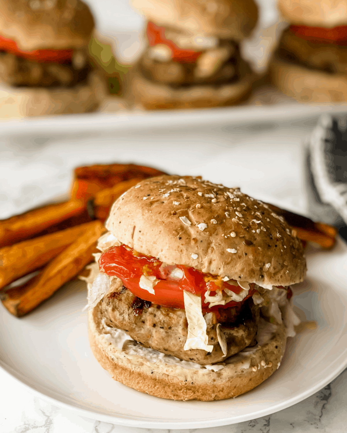 the best turkey burger recipe. A turkey burger on a whole wheat roll with sweet potato fries in the back.