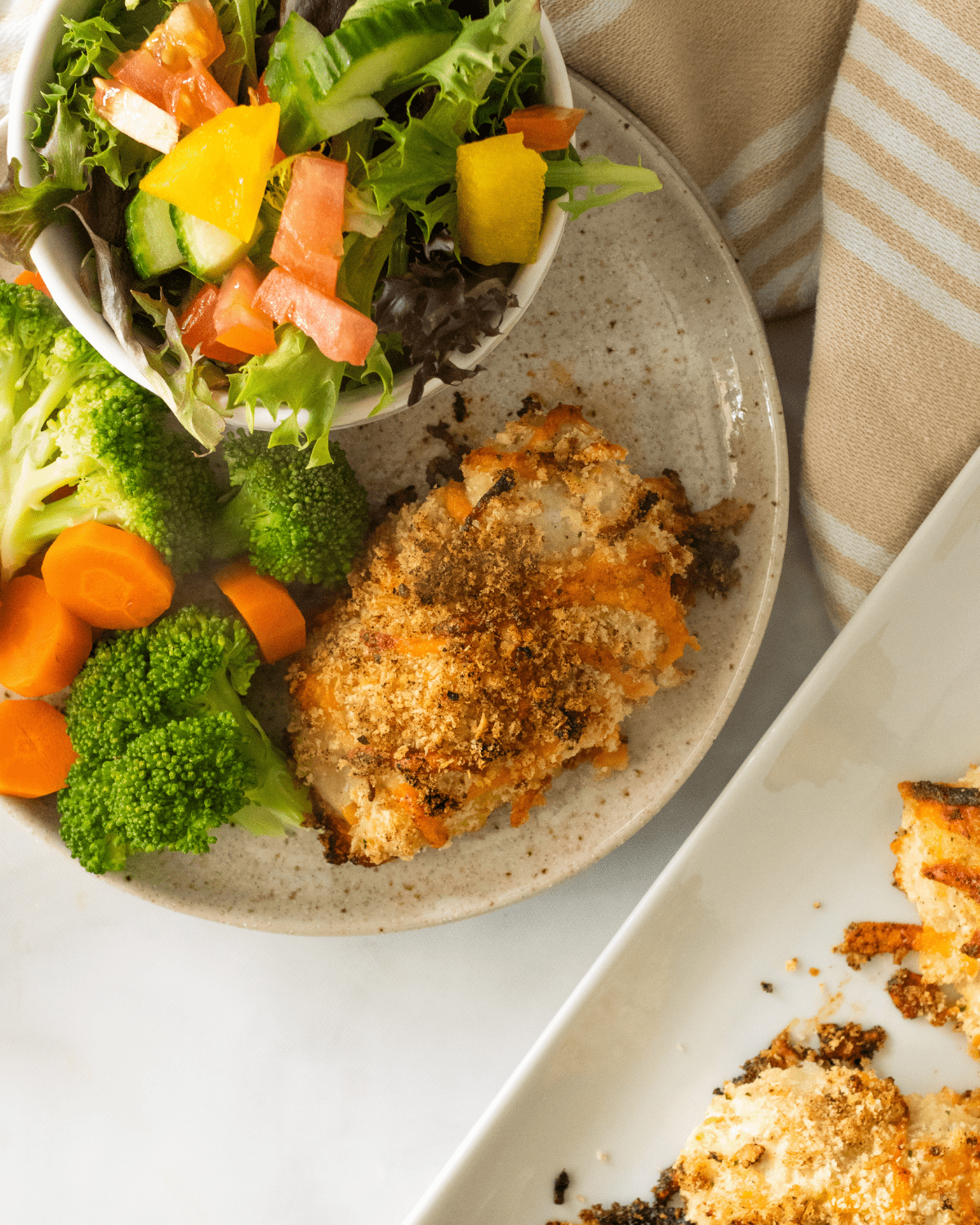 baked ranch chicken in a plate with broccoli and carrots.