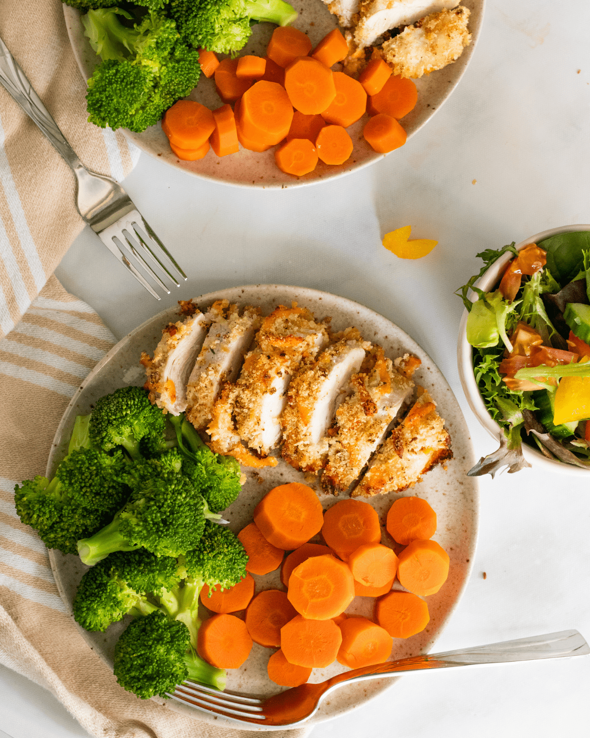baked ranch chicken on a plate with vegetables and a side salad.