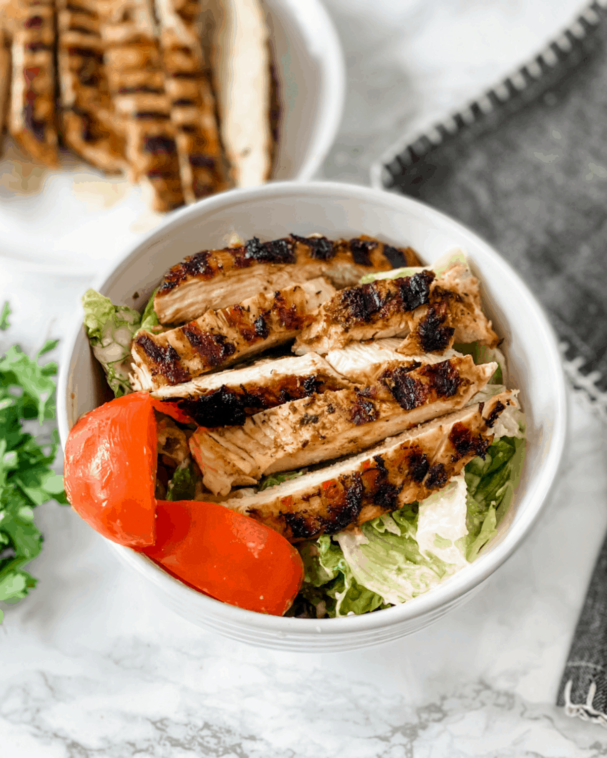 strips of grilled chicken on top of a salad.