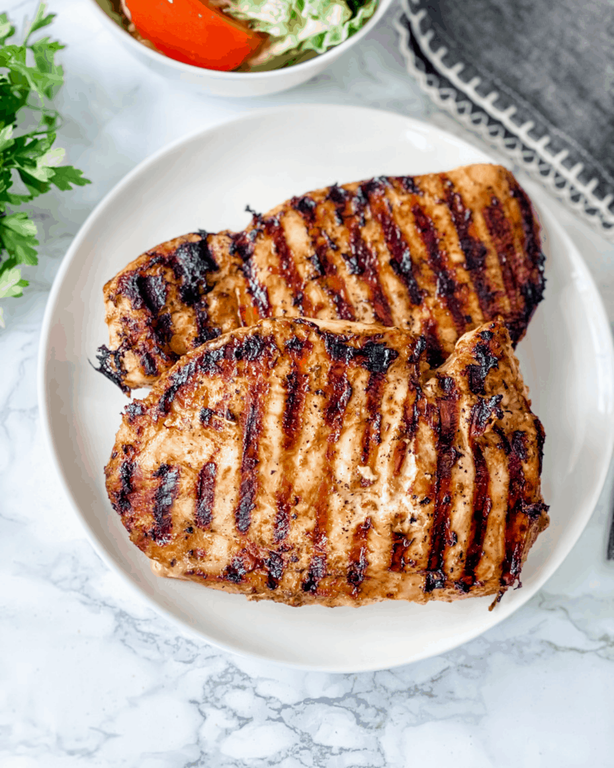 two pieces of grilled chicken on a plate