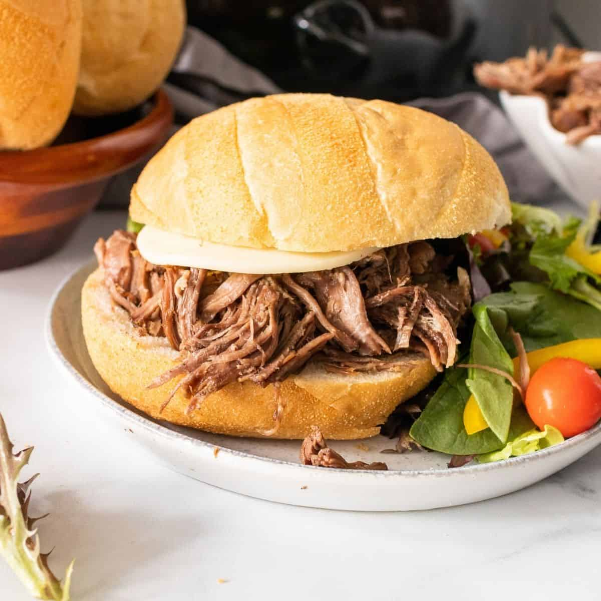 Slow cooker pot roast with onion soup mix shredded and on a roll
