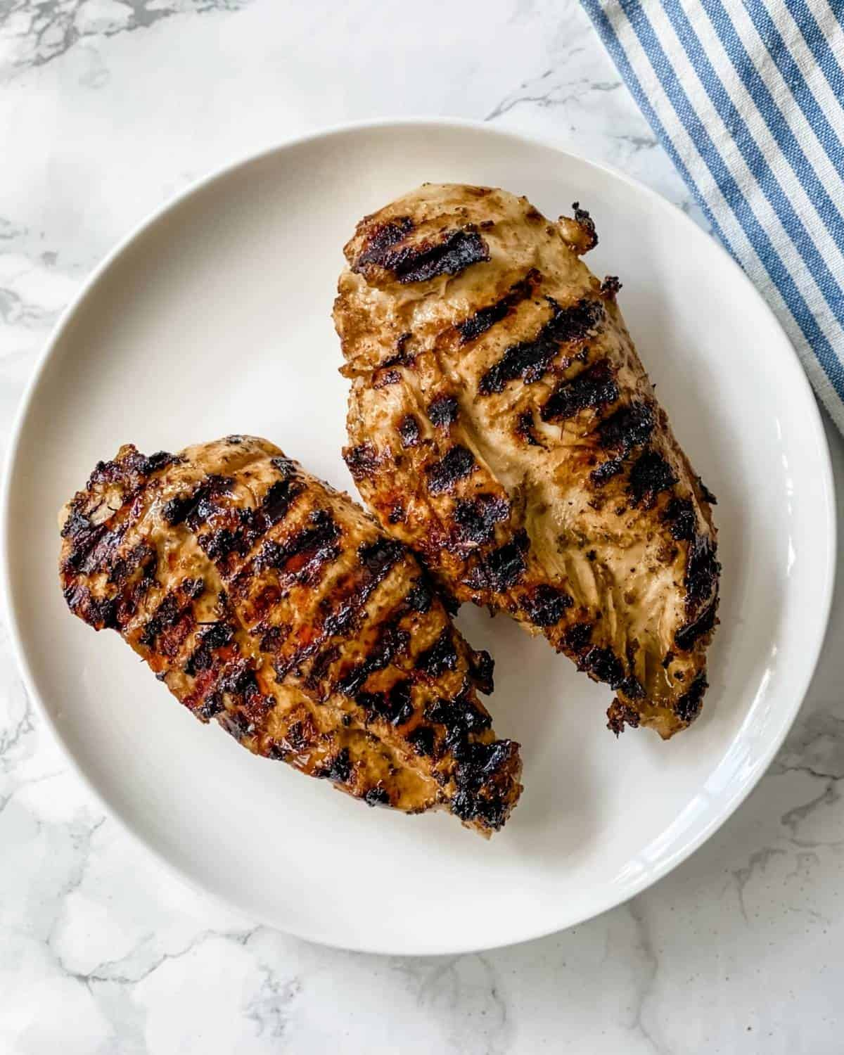 two pieces of grilled chicken breasts on a plate