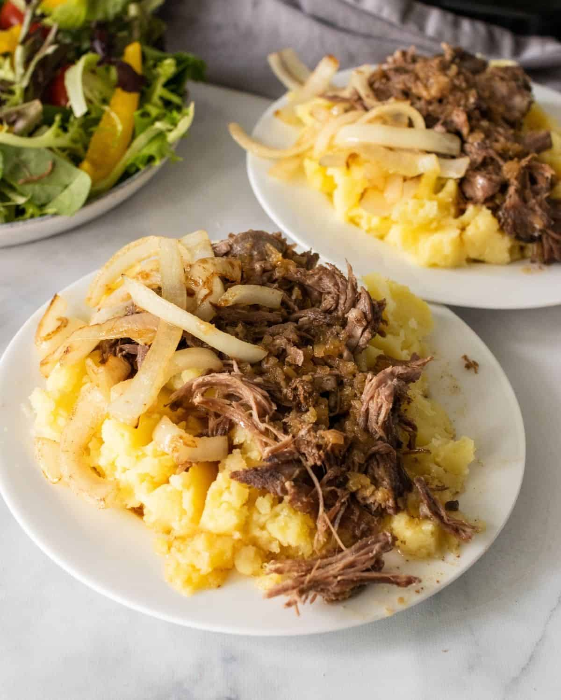 Plates of mashed potatoes and crockpot pot roast with a side salad