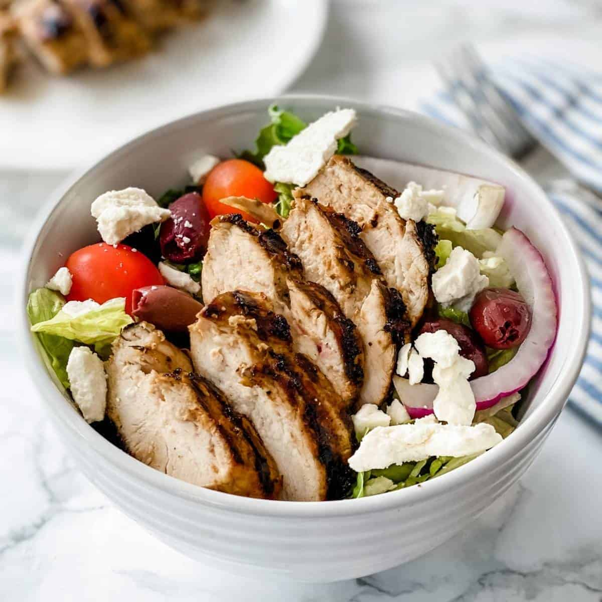 greek chicken marinade on a Greek Salad in a bowl