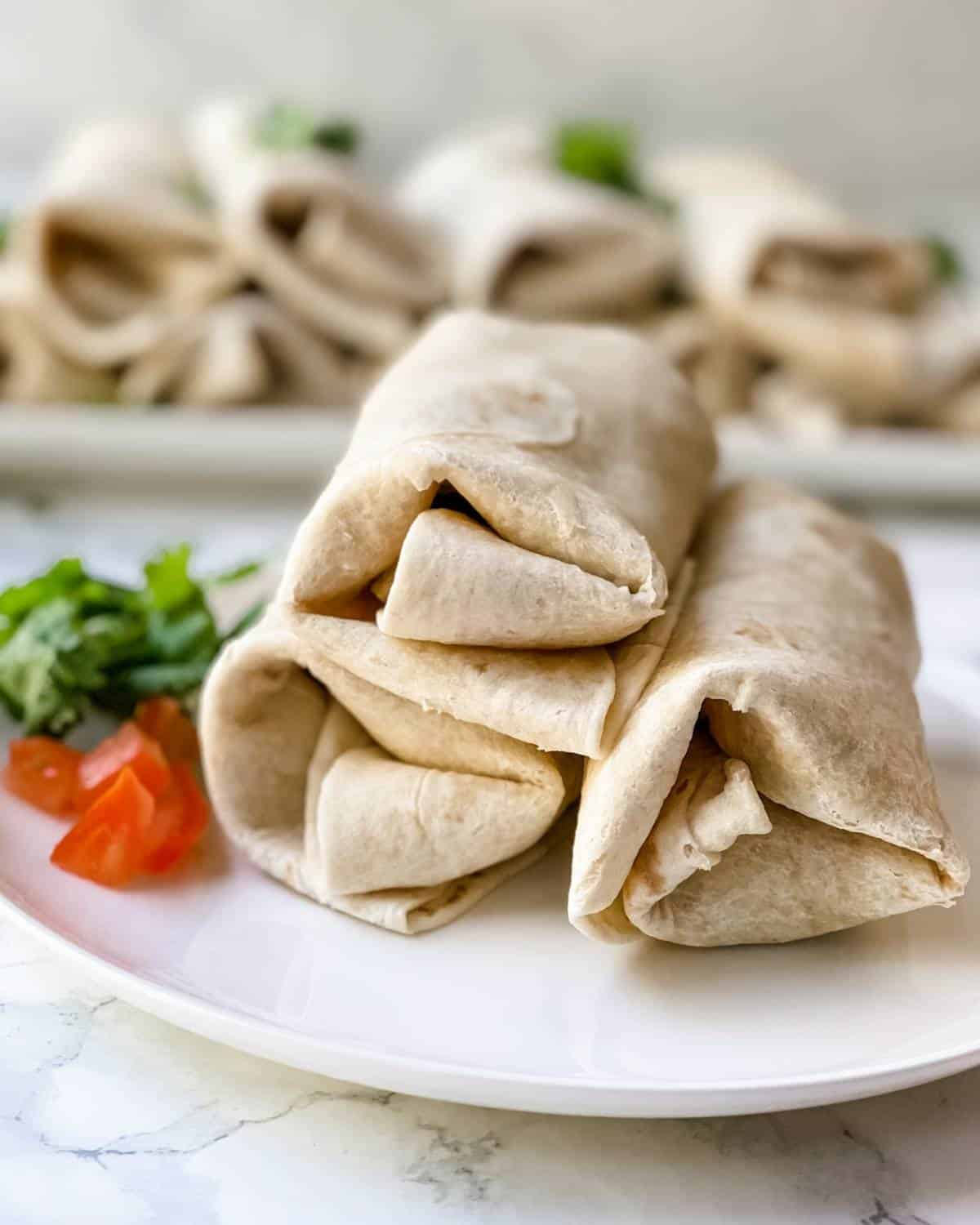 breakfast burritos that are prepared and on a plate
