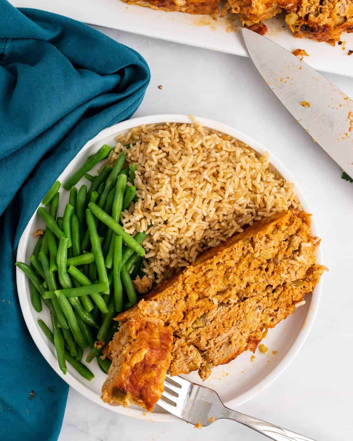 One slice of meatloaf on a plate with green beans and brown rice.
