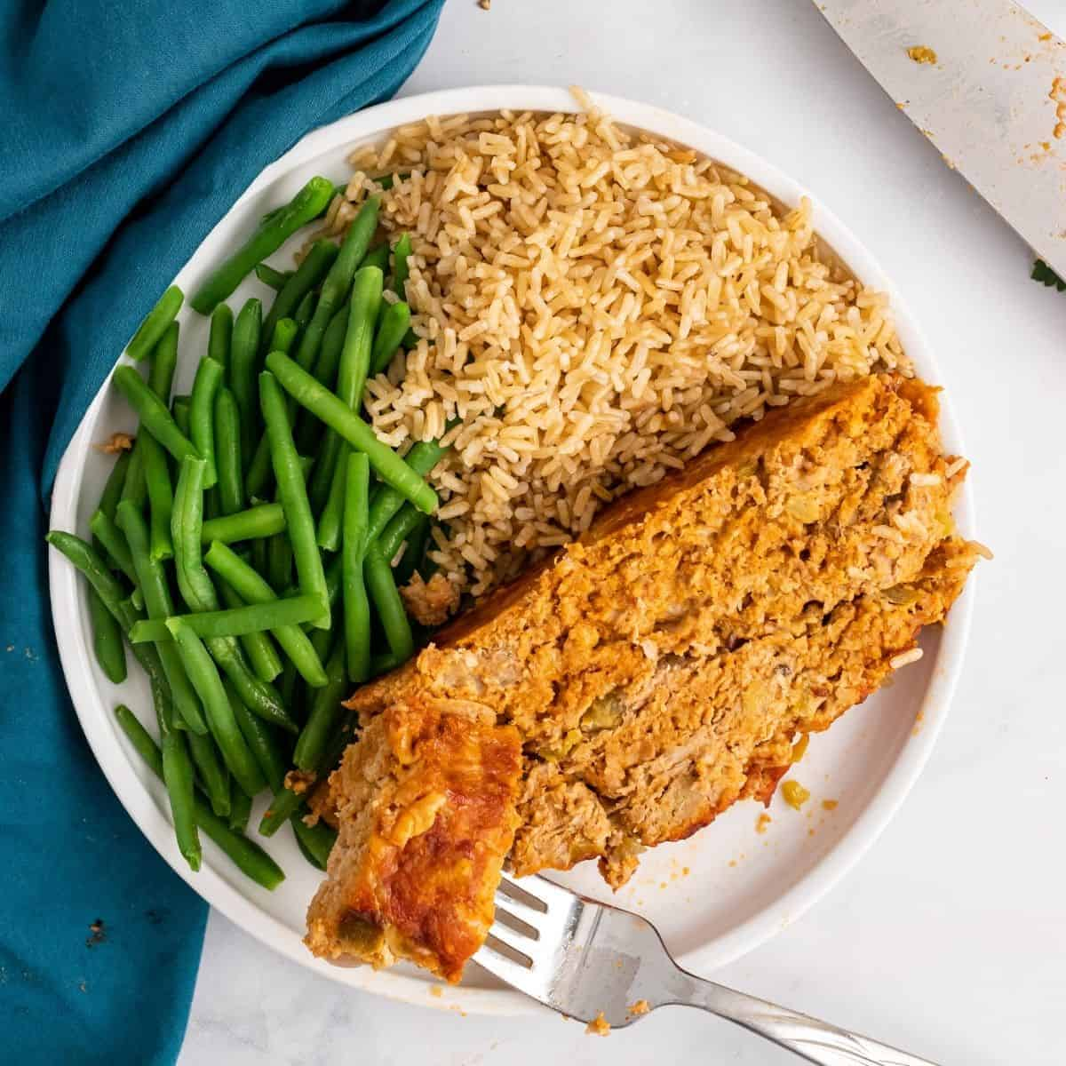 the best healthy meatloaf sides. meatloaf, rice, and green beans on a plate.