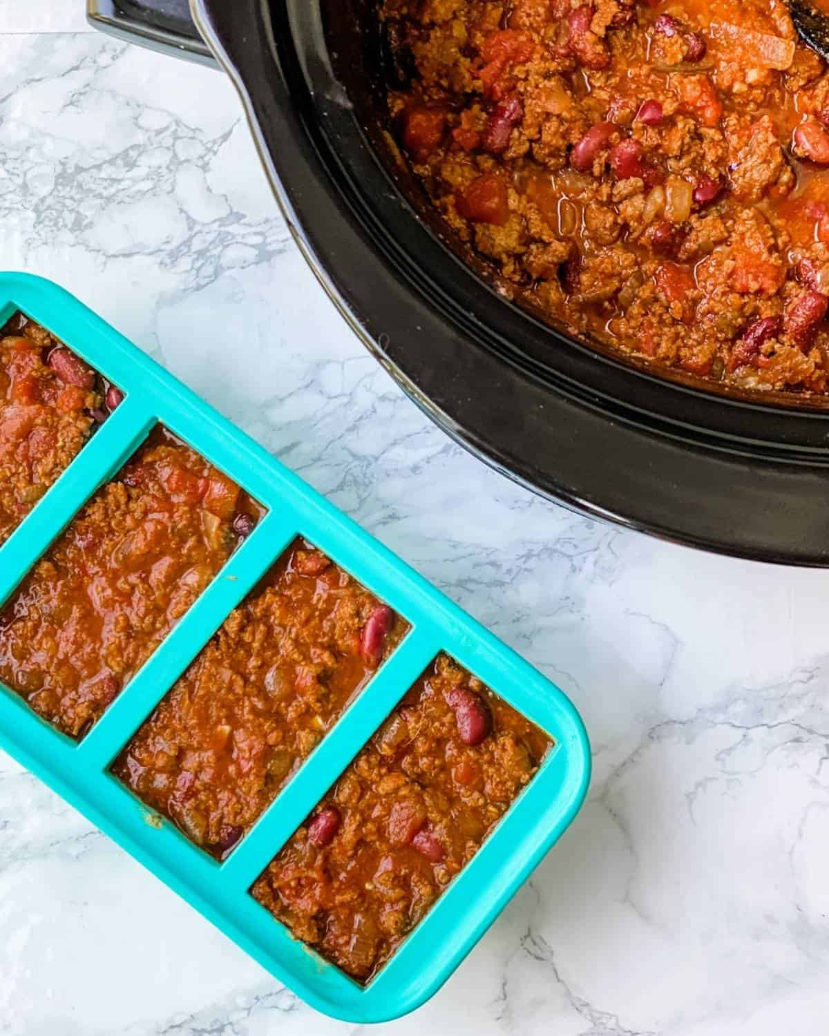 silicone souper cube trays with chili next to a slow cooker of chili