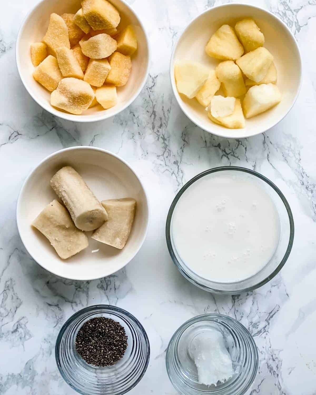 tropical smoothie ingredients. Pineapple, mango, banana, coconut milk, coconut oil, and chia seeds.