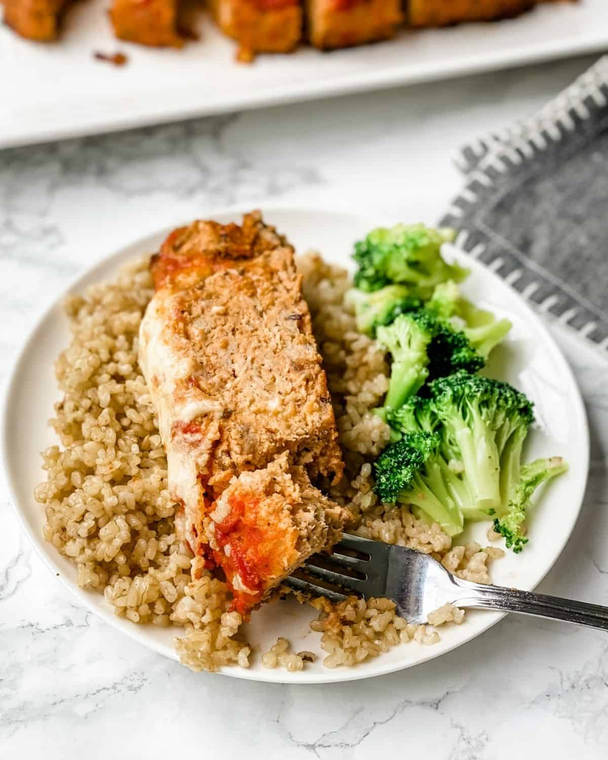 a slice of Italian meatloaf on a plate with rice and broccoli.