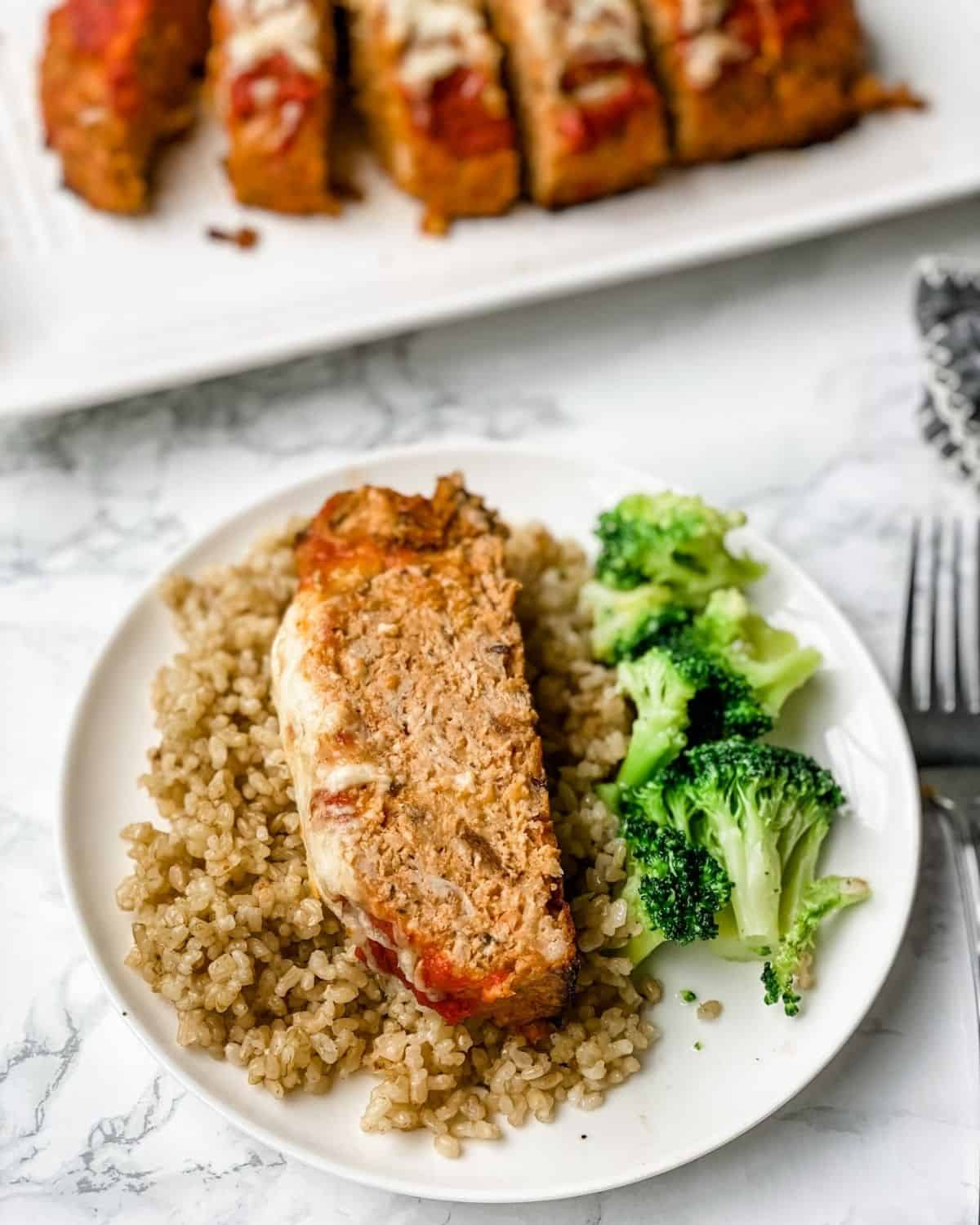 Italian meatloaf on a plate with rice and broccoli with a platter of sliced meatloaf in the background.