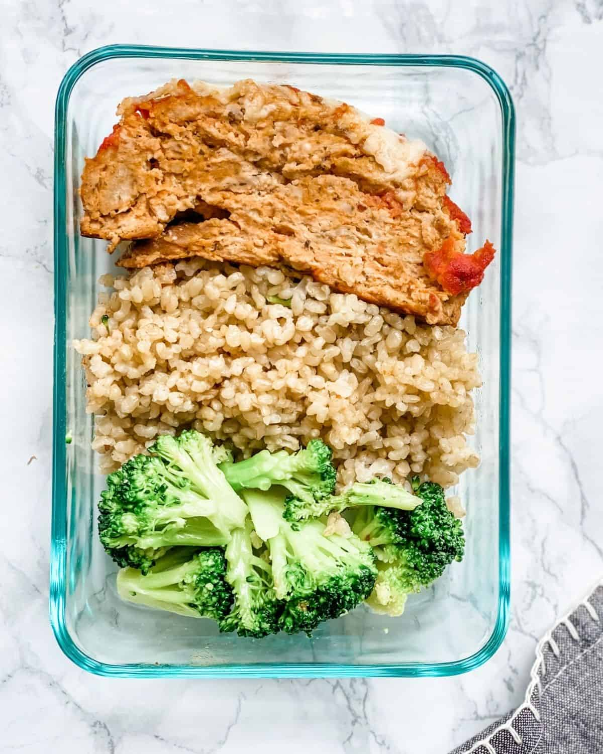 Italian meatloaf in a container with rice and broccoli.
